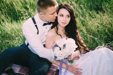 Newlyweds in love are sitting on the grass in the park. the bride and groom smile and have fun at the wedding picnic.
