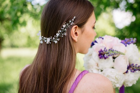 Bridesmaid with luxurious colorful wedding bouquet of peonies and other flowers with professional makeup and wedding crown tiara crest accessories turned away in purple violet dress.