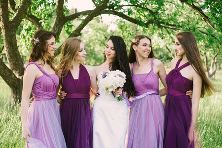 Emotional bride and bridesmaids are talking and smiling. Sexy caucasian girls in purple dresses having fun in the park, outdoors.