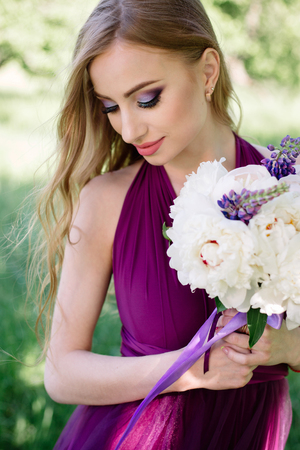 Bridesmaid with luxurious colorful wedding bouquet of peonies and other flowers with professional makeup standing at the ceremony among green trees. Stok Fotoğraf