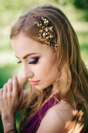 Bridesmaid with luxurious colorful professional makeup and wedding crown tiara crest accessories standing at the ceremony.
