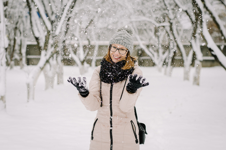Young attractive girl in nerd glasses, a beige down jacket and knitted hat with a pompon smiles and fools around, throwing snow with her arms.