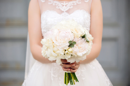 Beautiful young bride holds wedding bouquet of pastel beige tones peonies in hands with french manicure on blured background Stok Fotoğraf