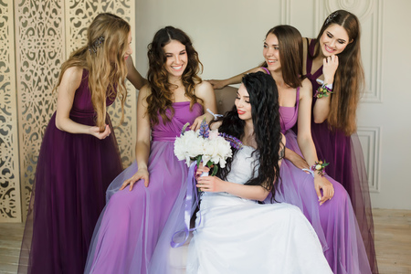 Felling excited about wedding. Attractive young bride holding a wedding bouquet and smiling while talking to her charming bridesmaids in purple dresses