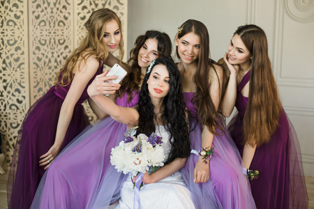 Bridesmaids taking a selfie on a smartphone and laugh during the morning of the bride at home. Beautiful girls in purple wedding dresses and bride with bouquet of peonies have fun.