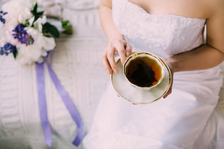 Sexy tender bride in night gown or wedding dress with decollete drinking a cup of morning black tea in porcelain cup and saucer sitting on the sofa. Purple and white bouquet Stok Fotoğraf