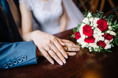 bride and groom in a cafe. wedding bouquet of roses on a wooden table in a restaurant, bride and groom hold each others hands. Wedding rings. Loving couple in a cafe. hot tea for lovers