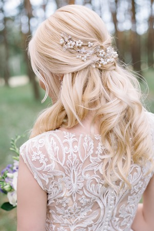 Portrait of lovely young bride with beautiful blond hair and curled hairstyle turned away on green background. Hair accessory: tiara, crown, beads Stok Fotoğraf