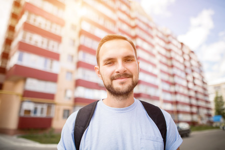 Happy funny bearded student man in blue t-shirt with backpack standing in front of the new building flat house dormitory. Hipster posing for photo smiling looking at the camera.