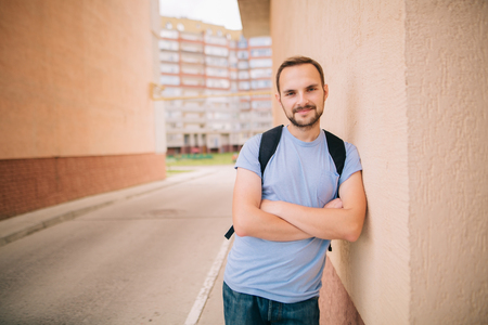Smiling caucasian bearded student young man hipster in blue t-shirt with backpack standing in arch leaning on wall in pastel beige tones near new building with his arms crossed closeup view.