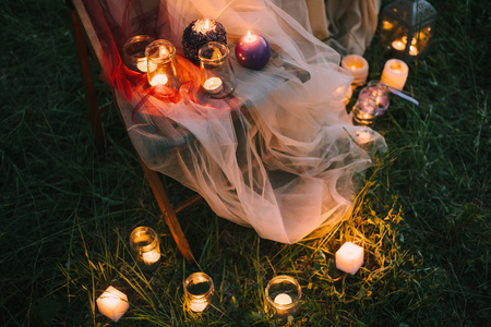 Night fine art outdoor wedding details: summer or spring ceremony with decor lowlight candles standing on chair covered with veil or soft tulle pastel tones and on the grass