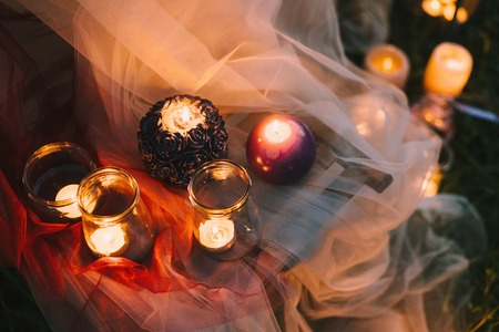 Night fine art rustic outdoor wedding details summer or spring ceremony with decor burning lowlight candles standing on table covered with veil soft cloth tulle pastel tones and on the grass