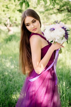 Portrait of bridesmaid luxurious wedding bouquet of peonies and flowers standing at ceremony in garden in purple violet dress smiling and looking at camera. Sunny day, final high school graduation Stok Fotoğraf