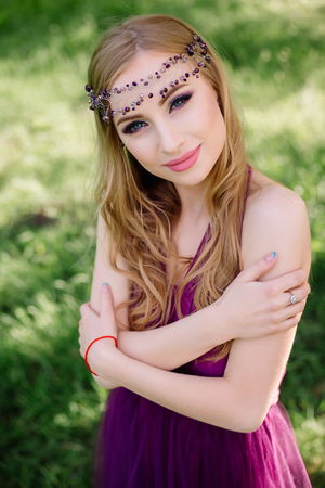 Sexy bridesmaid with luxurious wedding professional makeup and crown tiara crest accessories standing at ceremony in purple violet dress smiling looking at camera
