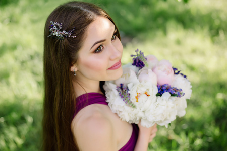 Bridesmaid with luxurious colorful wedding bouquet of peonies and other flowers standing at the ceremony in purple violet dress smiling and looking up hair vine wreath crystal rhinestones crown Stok Fotoğraf