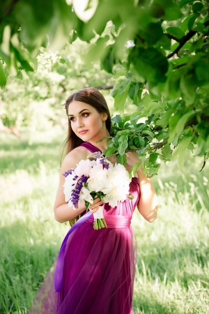 Bridesmaid with luxurious colorful fine art wedding bouquet of peonies and other flowers standing at the ceremony near tree in purple violet dress smiling and looking at the camera. Prom graduation Stok Fotoğraf