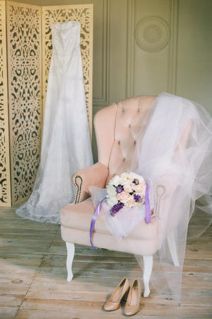 Fine art wedding dress with lace on wooden cabinet folding screen bouquet of peonies pink chair covered with soft cloth pastel tones Shoes on floor in hotel brides morning preparation closeup view.