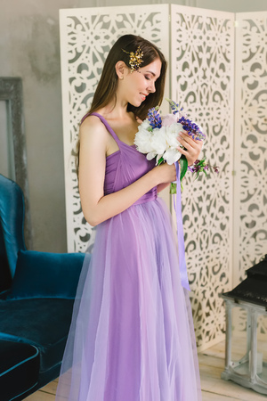 Bridesmaid in purple pink wedding dress and hair vine wreath crystal rhinestones crown tsmiles and look at bouquet of peonies during the morning of the bride in hotel. Preparation at home closeup view