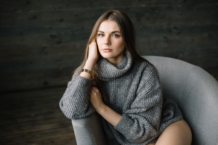 Dark haired sad woman in long grey knitted cozy sweater sitting in a chair at home near big window. Happy and Healthy girl with long beautiful legs with soft skin in studio. Stok Fotoğraf