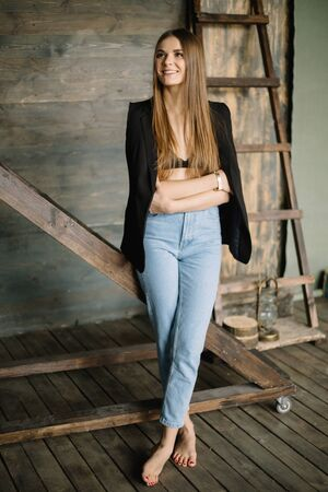 Portrait of beautiful smiling brunette girl posing against of wooden textured wall barefoot near ladder looking away with crossed arms in blue jeans with jacket and vest on shoulders. Stok Fotoğraf