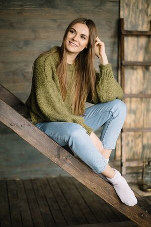 Grunge fashion: cute young girl informal model in blue jeans, dark knitted sweater and white socks sitting on the ladder smiling on the wooden background
