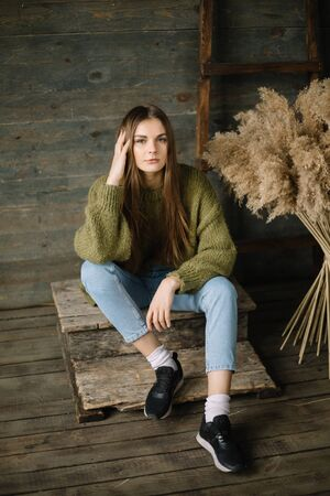Fashionable brown haired dreamy model girl sitting on wooden background floor. rustic studio in dark green knitted sweater and blue jeans. Fashion pose, arm near head, looking at camera Stok Fotoğraf