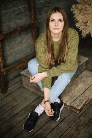 Trendy brown haired model girl sitting on wooden background floor. rustic studio in dark green knitted sweater and blue jeans.