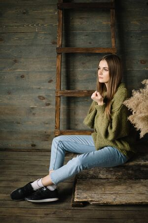 young beautiful brunette girl in a warm knitted. jeans and sneakers posing in studio with daylight.