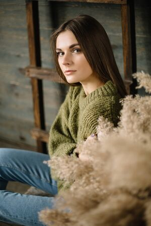 Gloomy brunette girl in a warm sweater in jeans and sneakers posing in studio with daylight. wooden background, ladder near wall Stok Fotoğraf