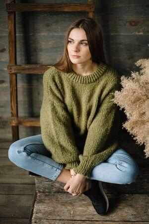 Sad brown haired dreamy model girl sitting cross-legged yoga style on wooden background floor. Stok Fotoğraf