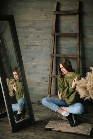 pretty woman in a marsh knitted cozy sweater with hay composition near the old wooden wall background with ladder on the wall.