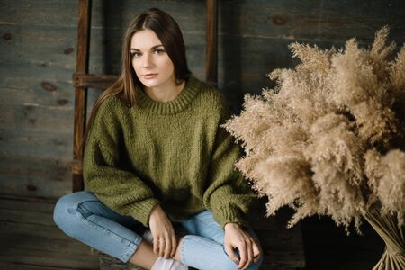 Sad young dark haired woman in a warm knitted dark green sweater, jeans posing in studio with daylight.