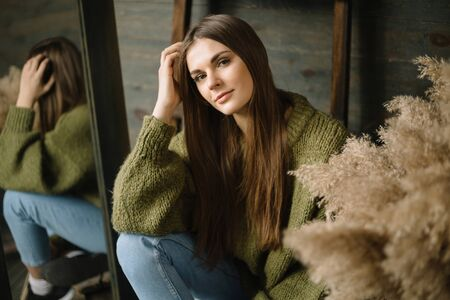 mysterious smiling young girl in dark green knitted cozy sweater with the sheaves of hay composition and mirror reflection