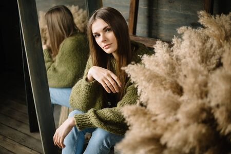 mysterious smiling young girl in dark green knitted cozy sweater sitting on the floor. Studio conceptual photo Stok Fotoğraf