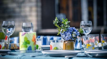 Table set outside for lunch or dinner  The table is decorated with spring flowers and colorful glassware  It is a sunny day in a countryside  photo