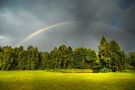 rainbow scene: Real rainbow against a stormy sky a beatiful green countryside in summer Stock Photo