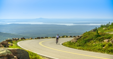 Female mountain bike cyclist riding downhill along  Mountain road in Acadia National Park, a clear summer day with panormic view of Acadia National Park  Maine, USA  landscape with lakes  photo