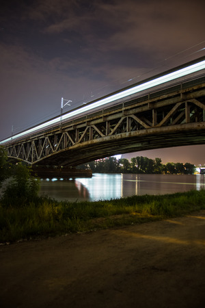 Bridge by night  Train bridge with lights and dark sky, National Stadium by Vistula river  Illuminated railway bridge in Warsaw, Poland  Europe  photo