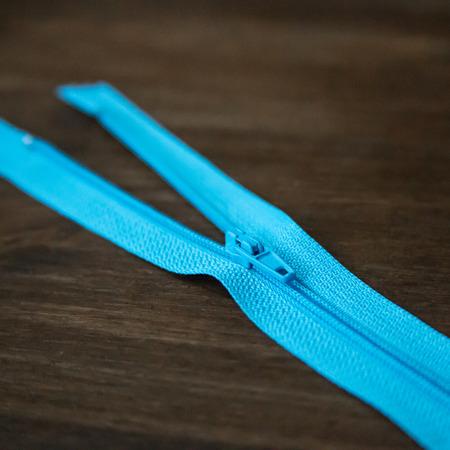 Blue clothing zipper closeup on dark wood background photo