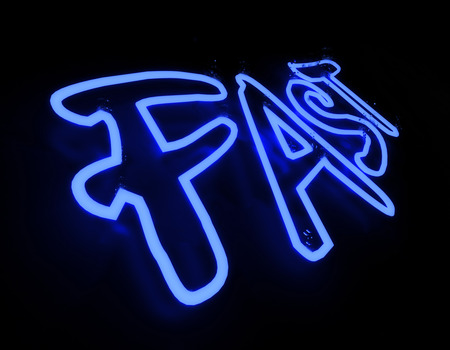 Fast neon sign isolated on black background Stock Photo