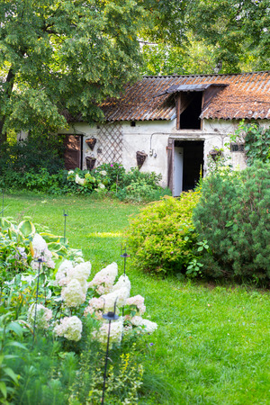 abandoned: Old cottage farm house in summer garden Stock Photo