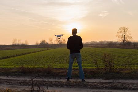 Mannen met drone vliegen bij zonsondergang