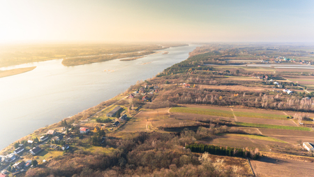 Drone aerial landscape view from above  with farmland and river in autumn sunset