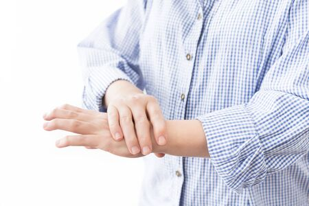Young woman in casual blue shirt suffering from pain in hands. Health care concept with real rheumatoid arthritis disease deformed fingers and hand.