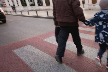 Crossing the road at a pedestrian crossing. A man with a child quickly go through the road. Car did not give way to the pedestrian Foto de archivo