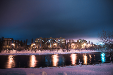 the little river and the multi-storey houses at the distant shore at snowy night