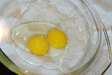 Broken yellow chicken eggs on a dish Stock Photo