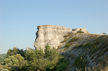 Lonely rock among trees and sunny sky