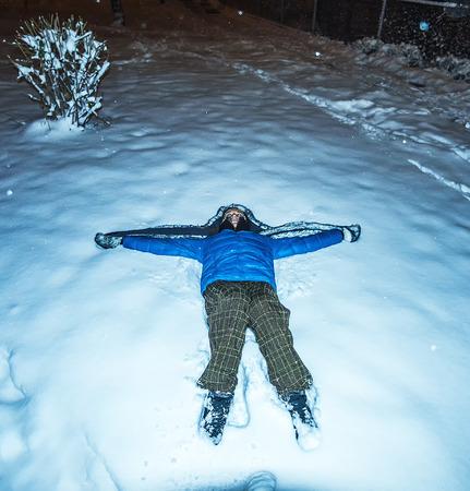 night dress: girl blue jacket furhat lying  snow at night