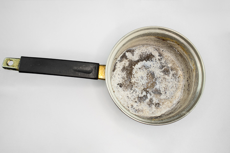 Pan with burnt food on white background